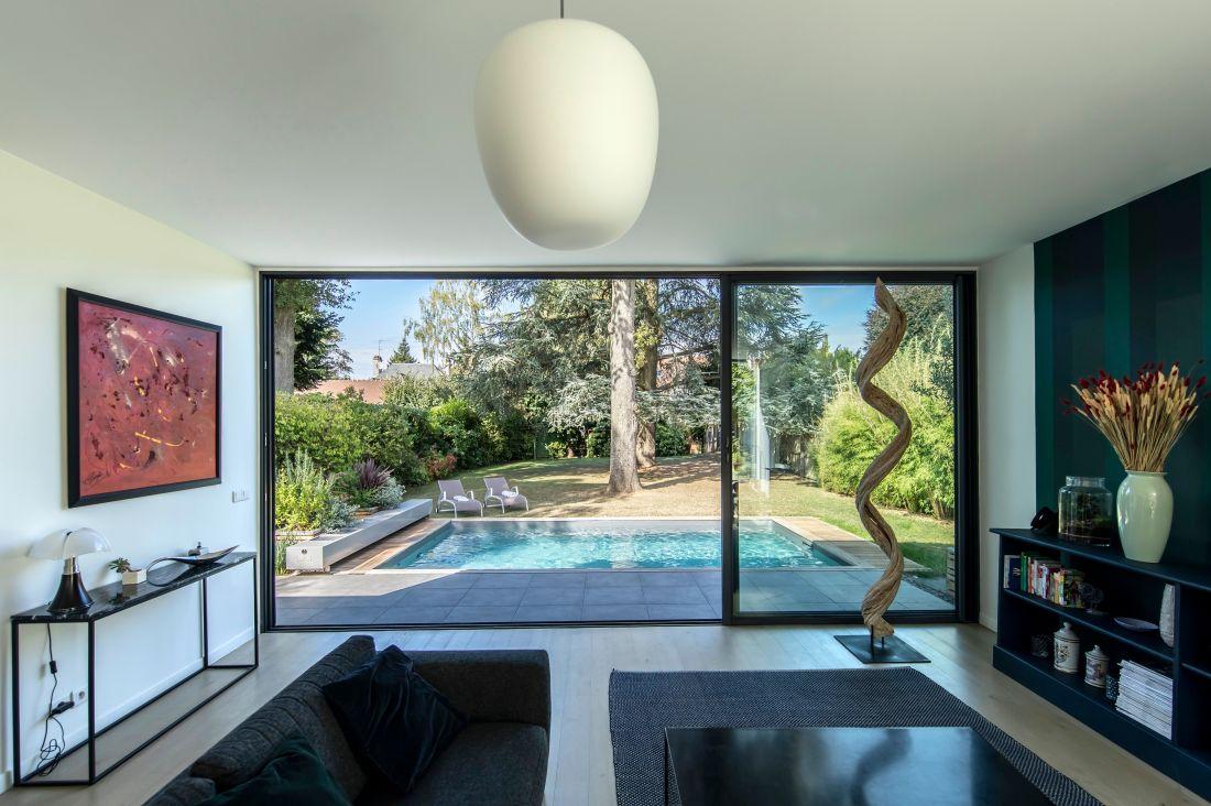 Depuis le salon empreint d'un esprit design, le goût du détail s'étend jusqu'au jardin et à la toile mobile bleue que forme la piscine.