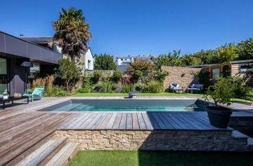 La piscine est semi-enterrée d'un côté permettant de gérer le dénivelé naturel du terrain et d'être au niveau de l'annexe de la maison.