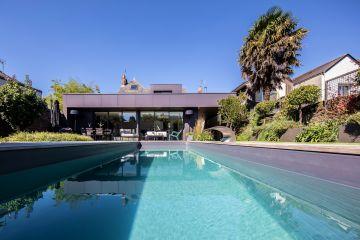 La piscine et son liner gris ardoise sont en harmonie parfaite avec le bardage en zinc de l'extension de maison moderne.