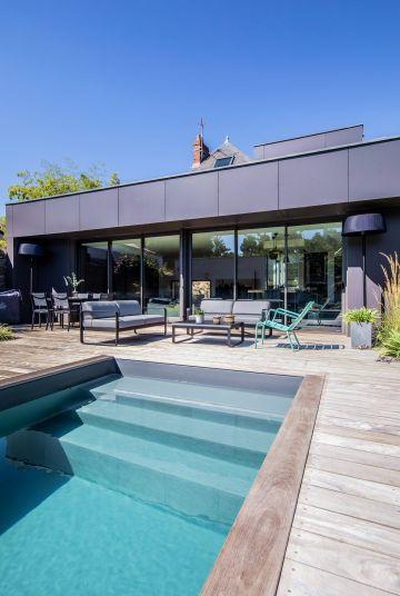 L'extension de la maison est ultra-contemporaine faite de grandes baies vitrées et d'un bardage en zinc rappelant les toits de Paris.