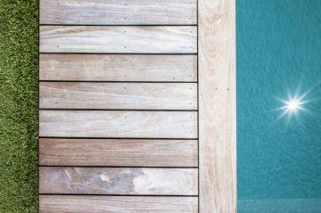 Les tons, les matériaux et la géométrie d'une piscine citadine aux lignes épurées.