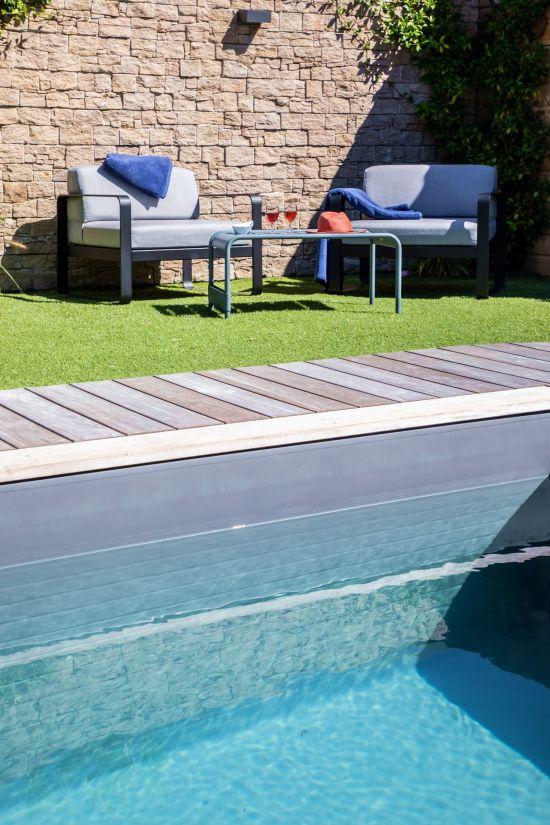 Un joli salon de jardin Fermob adossé à un mur de pierres sèches à quelques mètres de la piscine.