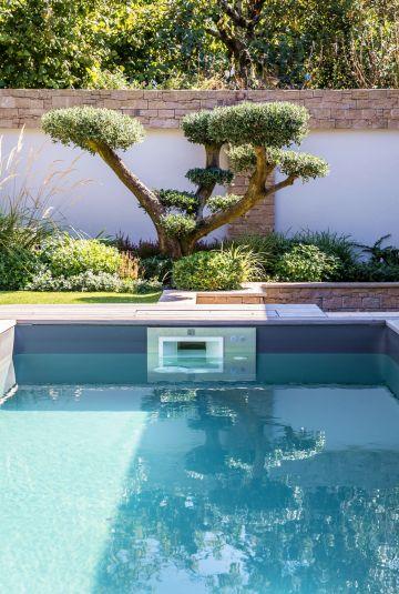 Dans le prolongement de la piscine un arbre taillé en bonsaï apporte une aura zen à la composition de l'espace extérieur.