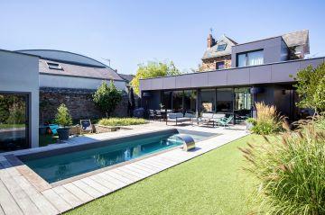 Totalement citadine la piscine est en harmonie parfaite avec la maison et son extension contemporaine en zinc.