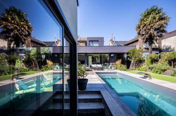 La piscine se reflète dans les baies vitrées de l'annexe de la maison pour une image surprenante de modernité.