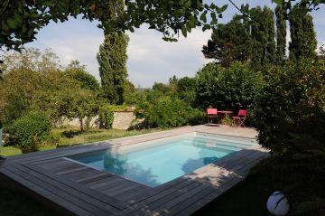 L'espace piscine est sur une terrasse dominant le verger plus bas et les champs au loin.