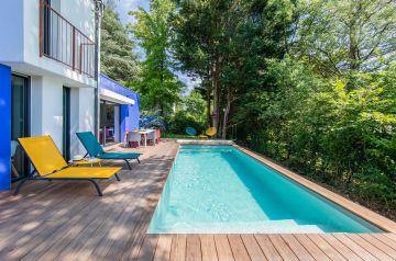 Les couleurs autour de la piscine créent une ambiance déco pop qui tranche avec la nature présente aux abords immédiats du bassin.