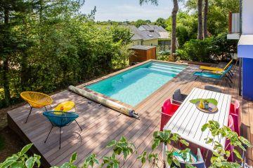 Fauteuils Acapulco assortis aux bain de soleil, sièges rouges pour le déjeuner, lignes contemporaines de la table et de la terrasse plus une piscine tirée à quatre épingles... l'ensemble réjouit au premier coup d'œil.