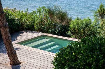 Cernée par les végétaux hirsutes, dominée par un grand pin qui perce la terrasse environnante, la piscine est au plus proche de la nature et réussi le défi de s'y intégrer.