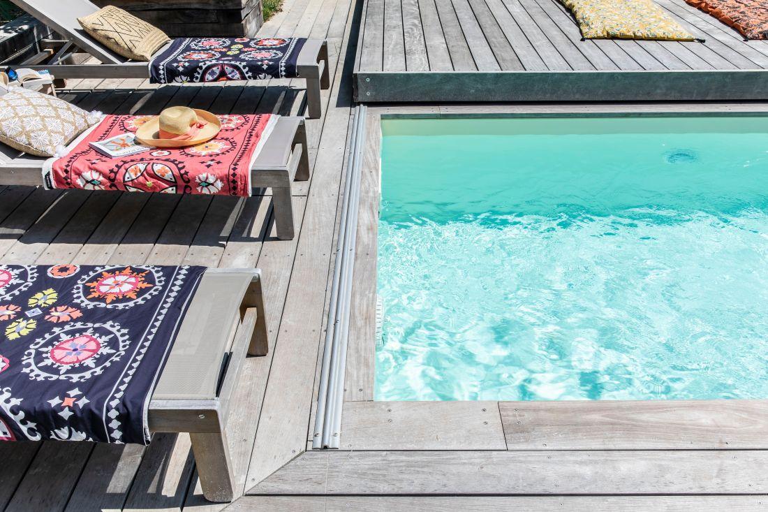 La texture de l'eau et sa couleur évoquent comme un tableau d'une vivacité atteignable par de rares maîtres. Les serviettes et les coussins nous rappellent à un usage simple et plaisant de la piscine.
