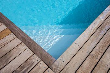 Le liner gris clair offre un plan d'eau lumineux qui fait varier les tons et les couleurs tout au long de l'année pour distraire chaque jour l'observateur de cette piscine traditionnelle en aluminium en Belgique.
