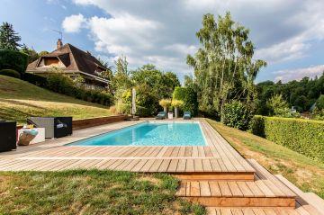 Un escalier réalisé sur-mesure permet de lier la terrasse de la piscine au niveau inférieur du jardin tout en conservant une cohérence dans les matériaux utilisés.