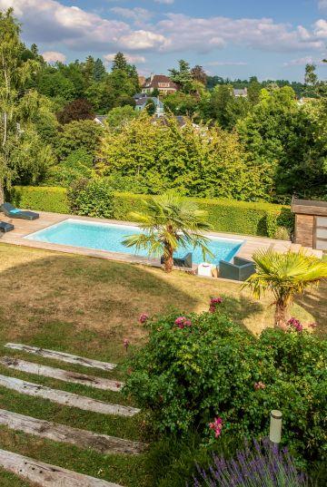 La piscine est implantée sur une terrasse en contrebas de la maison dans ce terrain en pente proche de Bruxelles.