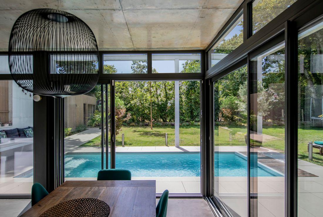 Depuis la table du salon, les heures de travail ou les déjeuners auront une douceur réhaussée par la présence de la piscine à quelques mètres.