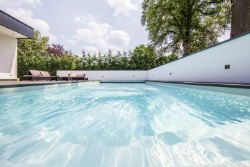 The sky over the Paris region, the crystal-clear pool water, and an elegant low wall surrounding the space give this Piscinelle pool its unique feel.