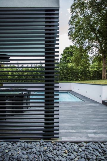 Behind a modern trellised panel reminiscent of an openwork fence is the blue pool providing a striking counterpoint to these grey shades.