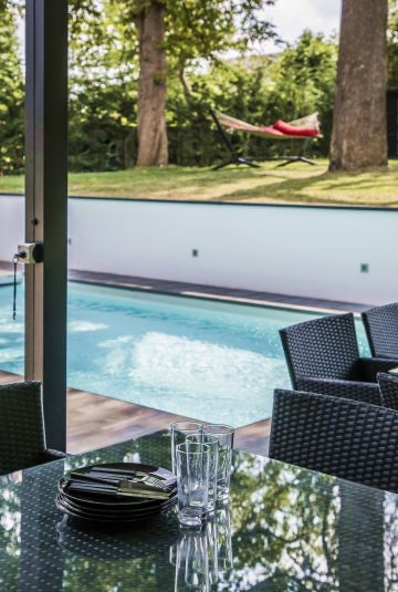 Reflections, with the discreet, minimalist, pool standing between a table set for lunch and a hammock.