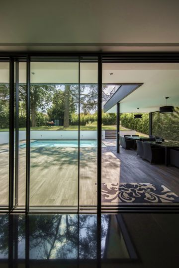 From inside the modern house, the pool is visible at the end of a high-end tiled patio.