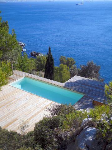 Une piscine rectangulaire Cr7 avec une terrasse au bord de la mer