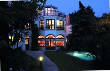 Piscine octogonale Rg éclairée dans la nuit avec une grande maison allumée