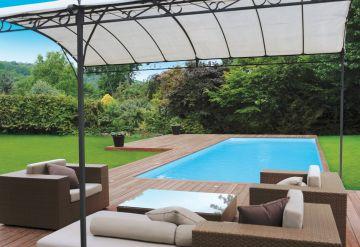 Une piscine rectangulaire Cr10 avec terrasse entourée d'une pelouse dans un jardin
