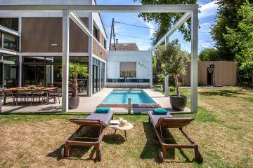 Le bardage bois verticale de la maison confère une modernité à l'espace piscine.