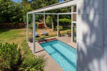 Aux heures d'été, entre un jardin ensoleillé et la fraîcheur de la maison se trouve une piscine atypique et accueillante.