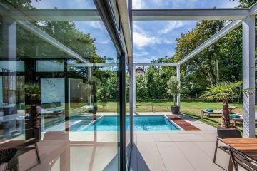 Dans la baie vitrée du salon se reflète le plan d'eau de la piscine et la structure aérienne donne un volume unique qui caractérise ce projet.