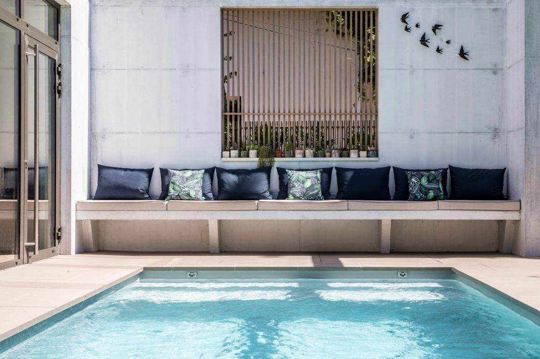 L'espace piscine a été conçu dès avant la construction de la maison permettant des aménagements très spécifiques comme cette banquette intégrée au bâti.