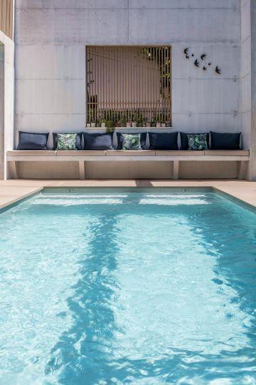 Cet espace piscine avec son aménagement très déco bénéficie d'une patine qu'on pourrait qualifier de luxe sobre, presque brutaliste avec cet usage revendiqué du béton brut.