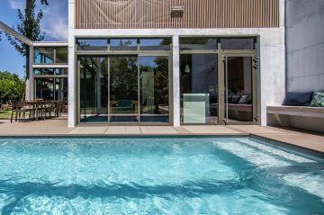 La modernité des matériaux utilisés ancre cette piscine dans son époque et lui donne une dimension architecturale qui dépasse son simple usage.