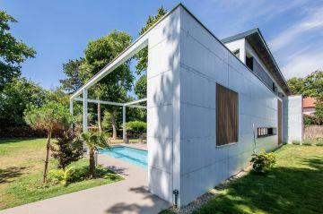 Le mur blanc ajouré reprend les persiennes verticales des bardages de la maison et apporte un design qui résonne avec les aménagements décoratifs qui entourent la piscine.