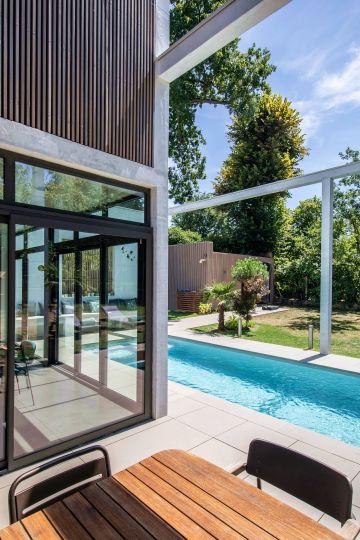 La structure de béton blanc semble matérialiser les murs de cette pièce extérieure que représente ici cet espace piscine atypique.