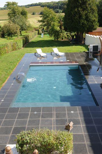 Une piscine Piscinelle installée en pleine campagne et entourée d'un beau dallage granité.