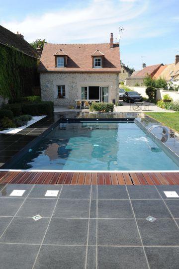 La piscine est positionnée devant la maison en pierre comme un grand miroir.