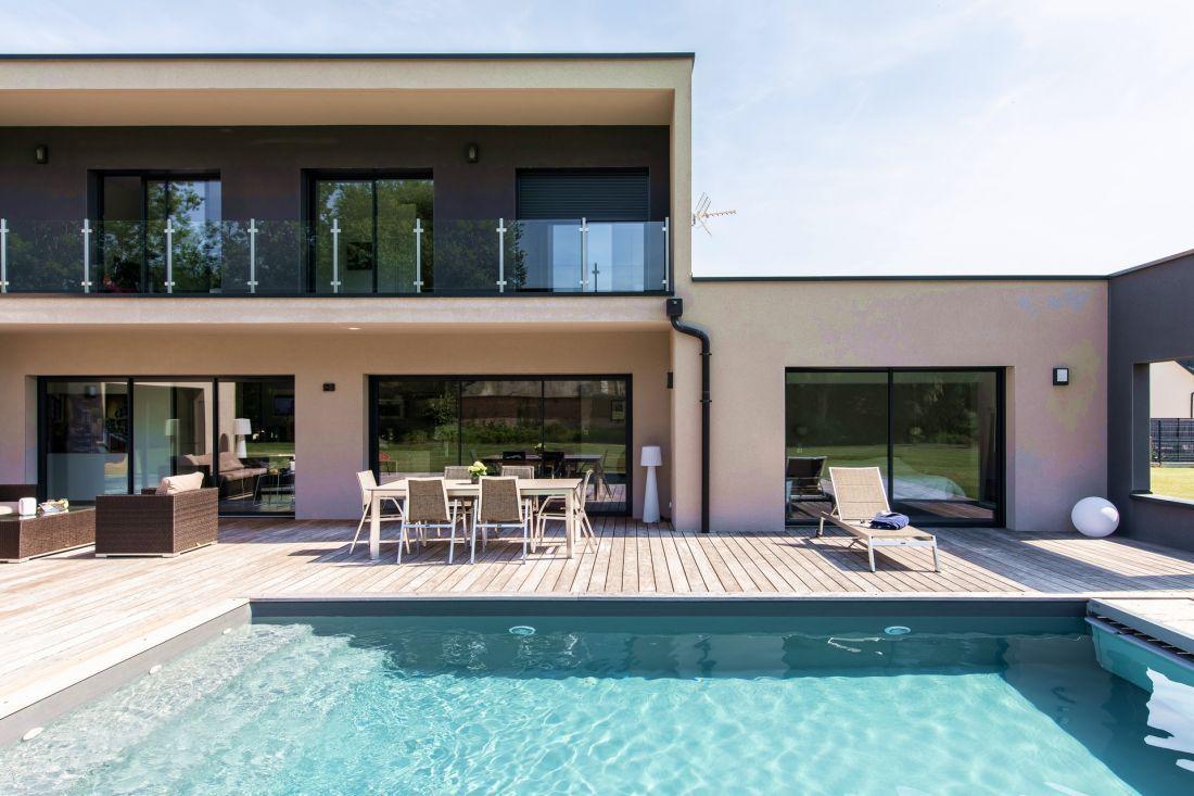 Piscine, terrasse et maison sont conçus dans une grand ensemble de lignes droites qui s'alignent et se croisent dans un vaste tableau aux couleurs pales.