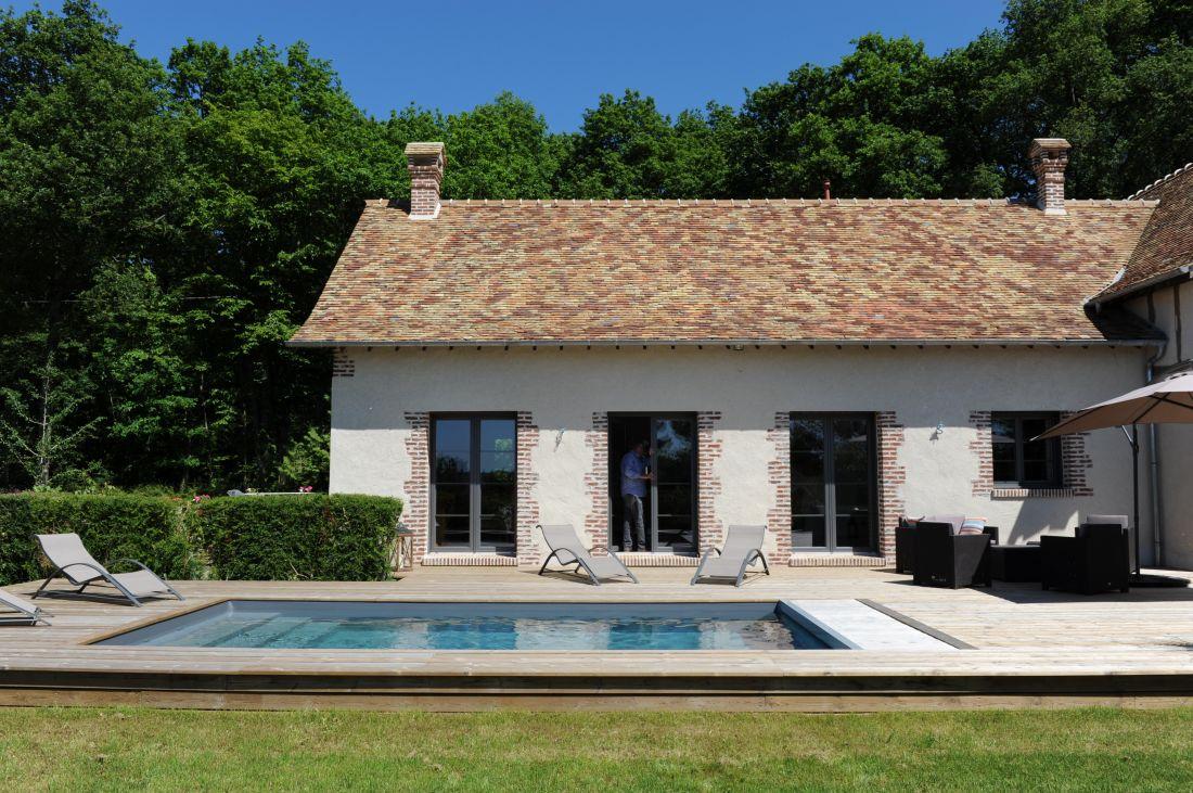Le camaïeu de tuiles orangées, marrons et beiges du toit rénové dans la plus pure tradition normande est d'une qualité exceptionnelle et se reflète sous certains angles dans la piscine.