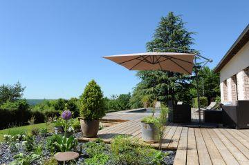 Entre des petits massifs paysagés, une belle terrasse en sapin et une longère traditionnelle normande Piscinelle a su construire un bassin intégré pour le plus grand bonheur des invités.