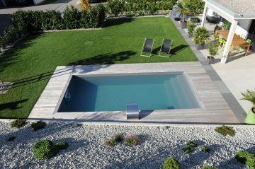 Une piscine rectangulaire dans un jardin entre pelouse et gravier