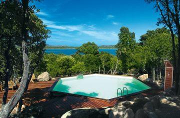 Une piscine Hx avec terrasse en bois avec une vue sur la mer