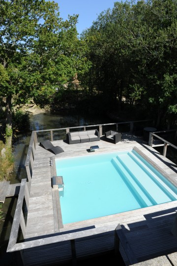 Piscinelle pool built in the middle of a lake with bespoke Escabanc step/tanning ledge unit