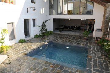 Petite piscine carrée de 10m² entièrement entourée de pierre naturelle jusqu'au bord de l'eau et dans le prolongement du sol de la maison.