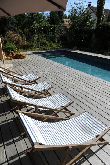 La large plage réalisée en bois d'ipé ajoute design et sérénité à la piscine en même temps quelle permet une circulation facile autour du plan d'eau.