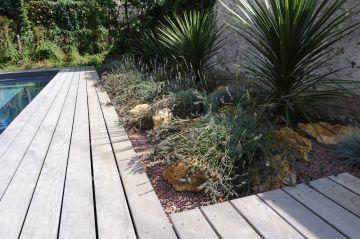 Les abords de la piscine traditionnelle sont paysagés avec quelque végétaux bien choisis.