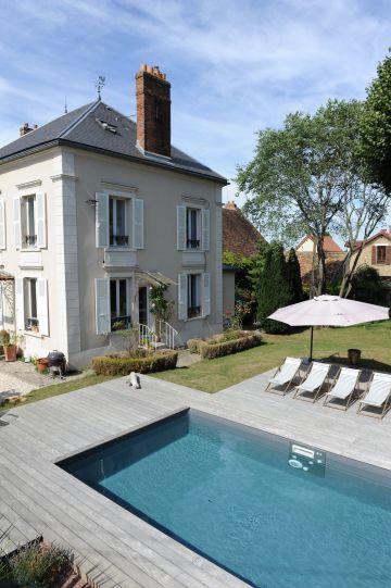 La piscine est au pied d'un bel hôtel particulier comme un miroir reflétant fenêtres et cheminées.