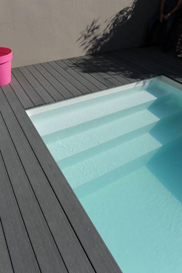 L'Escabanc permet de faciliter l'entrée et la sortie du bassin. L'absence de margelle et la terrasse en composite se terminant directement au bord du plan d'eau donnent un côté tendu et moderne à la piscine.