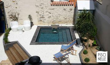 Petite piscine avec des margelles en pierre au milieu d'un petit jardin dans la ville