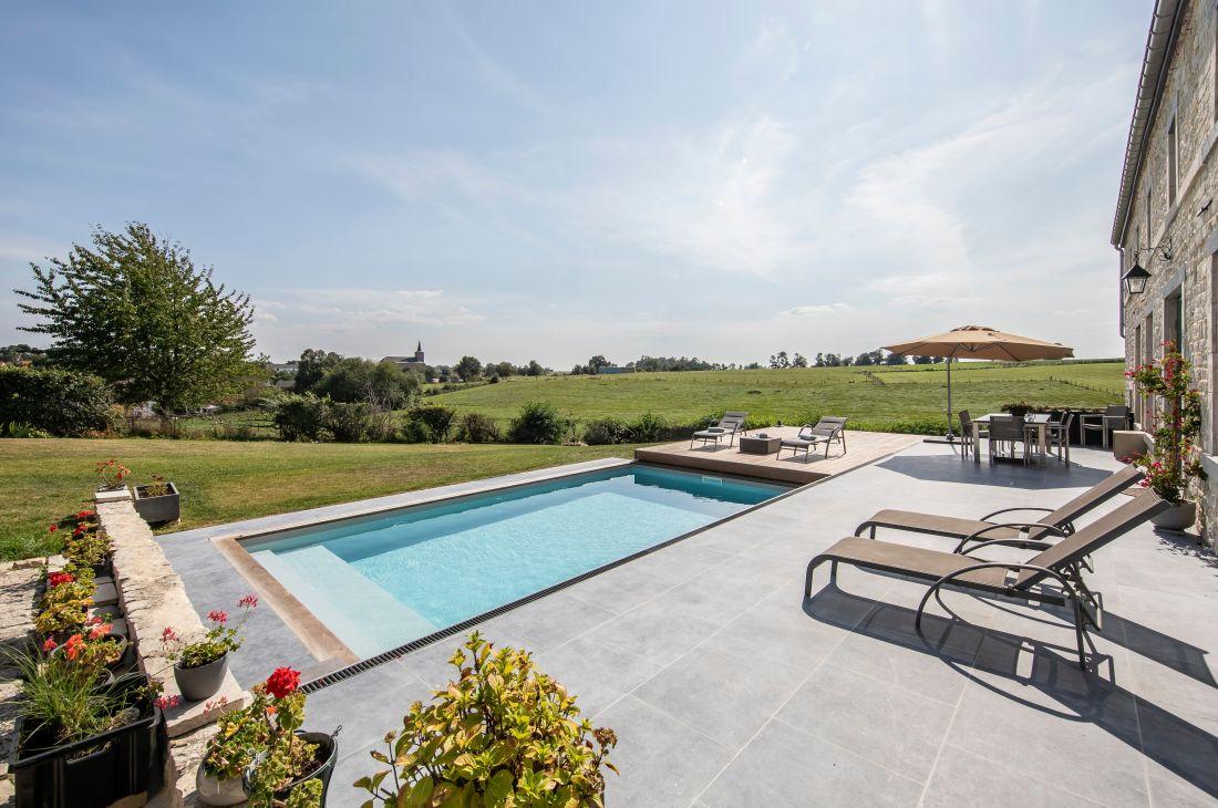 Le projet de rénovation mêle pierre bleu, piscine, bois et gazon pour un tableau d'une esthétique aboutie.