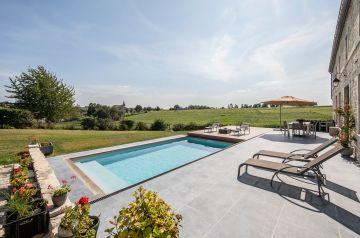 Au pied de la maison une superbe terrasse en pierre bleue de Belgique qui est alignée avec le Rolling-Deck de la piscine.