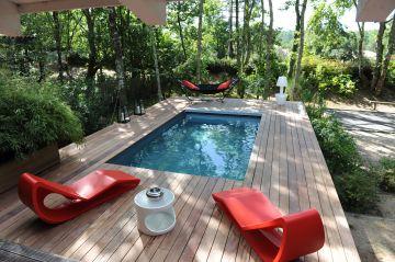Une piscine entourée de lamelles en bois